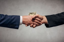 two businessmen shaking hands and exchanging money
