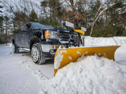 A truck with a snow plow removing snow