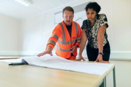 male construction worker reviewing blueprints with female client