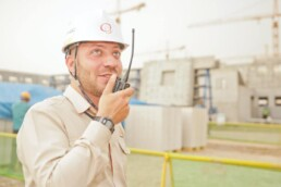 man wearing a hard hat at a job site and speaking into a walkie talkie