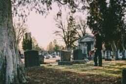 man paying respects at gravestone